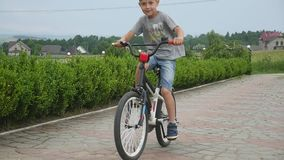 Kind het Cirkelen - jonge jongen die zijn fiets berijden op de weg stock video