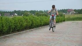 Kind het Cirkelen - jonge jongen die zijn fiets berijden op de weg stock videobeelden