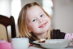 Kind het eten - vuile mond die - de camera onderzoeken stock foto