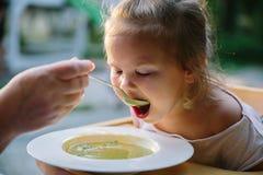 Kind het feading met soep bij de restauranttuin stock foto