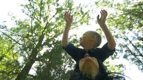 Kind het glimlachen terwijl status op moederschouders die van zijn het recreatieve tijd opheffen genieten dient lucht in stock videobeelden