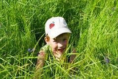 Kind in het gras Stock Afbeeldingen