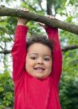 Kind het hangen op een boomtak Stock Foto's