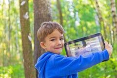 Kind in het hout met tabletpc royalty-vrije stock fotografie