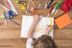 Kind het krabbelen in een notitieboekje Stock Fotografie