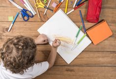 Kind het krabbelen in een notitieboekje Stock Afbeeldingen