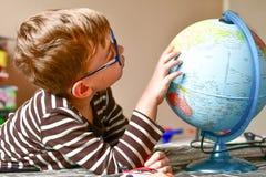 Kind het leren aardrijkskunde met bol thuis royalty-vrije stock afbeeldingen