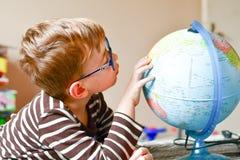 Kind het leren aardrijkskunde met bol thuis stock afbeeldingen