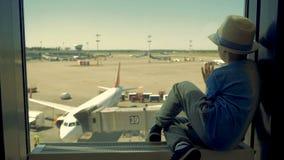 Kind het letten op de vliegtuigen die, sluiten omhoog laden Één jongen zit in een luchthavengebouw, bekijkend de vliegtuigen door stock video