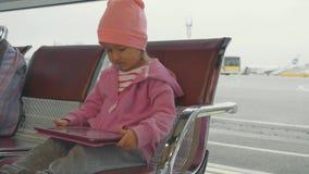 Kind het letten op tablet bij luchthavenvertrek launge stock videobeelden