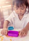 Kind het leuke meisje spelen met klei, spel doh Stock Afbeeldingen