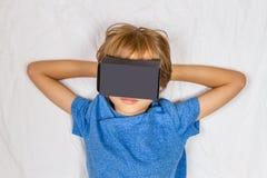 Kind het liying op bed met 3D Virtuele Werkelijkheid, VR-kartonglazen Royalty-vrije Stock Foto's