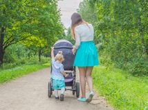 Kind in het Park die een wandelwagen duwen Stock Fotografie