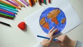 Kind het schilderen Aarde en overal het zetten van hartteken, vredeswereld, concept stock videobeelden