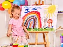 Kind het schilderen bij schildersezel Stock Foto