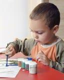 Kind het schilderen met borstel en kleuren Stock Foto's