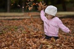 Kind het spelen met bladeren op de straat Stock Foto's