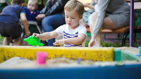 Kind het spelen met speelgoed in zand-kuil stock video