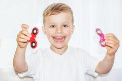 Kind het spelen met twee friemelt spinners Stock Foto's