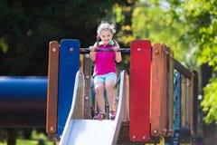 Kind het spelen op openluchtspeelplaats in de zomer Stock Fotografie