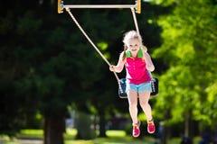 Kind het spelen op openluchtspeelplaats in de zomer Stock Foto