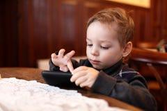 Kind het spelen op smartphone stock afbeeldingen