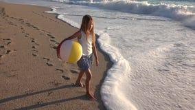 Kind het spelen op strand bij zonsondergang, gelukkig jong geitje die in overzees golvenmeisje lopen op kust, kust stock videobeelden