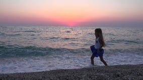 Kind het Spelen op Strand, Meisje het Lopen op Kustlijn, Overzeese Golven bekijkt in Zonsondergang 4K stock videobeelden