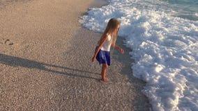 Kind het Spelen op Strand, Overzeese Golven bekijkt, Meisje het Lopen op Kustlijn in Zonsondergang 4K stock footage