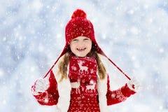 Kind het spelen in sneeuw op Kerstmis Jonge geitjes in de winter stock fotografie