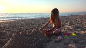 Kind het Spelen Zandkasteel op Strand bij Zonsondergang, Meisje op Kust, Kustlijn 4K stock video