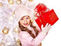 Kind in hoed en vuisthandschoenen die rode giftdoos houden. Royalty-vrije Stock Foto