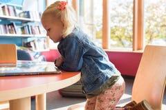 Kind in ihrer eigenen Welt hingerissen durch ein Buch Lizenzfreie Stockfotos