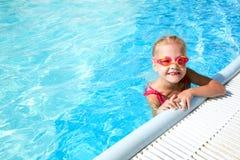 Kind im blauen Wasser des Swimmingpools Stockbild
