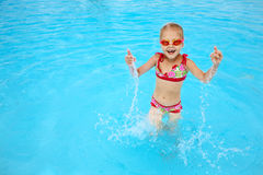 Kind im blauen Wasser des Swimmingpools Stockfotos