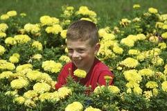 Kind im Blumen-Bett lizenzfreie stockbilder