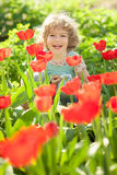 Kind im blumigen Garten Lizenzfreies Stockbild
