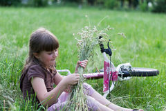 Kind im Gras mit Fahrrad lizenzfreie stockfotografie