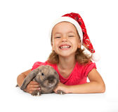 Kind im Hut des neuen Jahres mit einem Kaninchen. Lizenzfreies Stockfoto