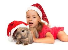 Kind im Hut des neuen Jahres mit einem Kaninchen. Lizenzfreies Stockbild