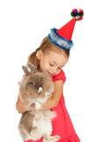 Kind im Hut des neuen Jahres mit einem Kaninchen. Lizenzfreie Stockbilder