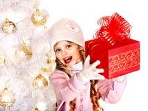 Kind im Hut und in Handschuhen, die rote Geschenkbox nahe Baum der weißen Weihnacht halten. Stockfotos