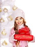 Kind im Hut und in Handschuhen, die rote Geschenkbox nahe Baum der weißen Weihnacht halten. Lizenzfreie Stockfotografie