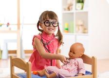 Kind im Kindergarten Kind im Kindergarten Kleines Mädchen, das Doktor mit Puppe spielt lizenzfreies stockfoto