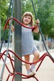 Kind im Kleid, das an den Seilen klettert Stockbilder