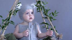 Kind im Kostüm der Maus sitzt auf dem verschobenen Schwingen, das mit grünen Blättern auf blauem Hintergrund geschmückt wird stock video footage