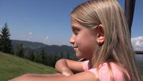 Kind im Sessellift, touristisches Mädchen in Ski Cable, Kind in den Bahnbergen, alpin stock footage