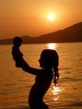Kind im Sonnenuntergang mit Schätzchen spielt auf Meer Lizenzfreies Stockfoto