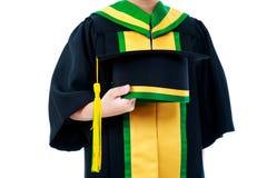 Kind im Staffelungskleid, das Kappe hält Lokalisiert auf weißem backgrou Lizenzfreie Stockfotos