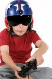 Kind im Sturzhelm, der einen Flugsimulator spielt Lizenzfreie Stockfotos